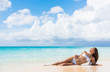 Sexy bikini body woman relaxing sun tanning on beach vacation lying down sunbathing on beach at tropical luxury destination in the Caribbean. Fashion, skincare solar protection, weight loss concept.