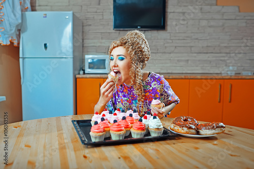 Photo Beautiful girl eating muffins in the kitchen, glutton, overeat