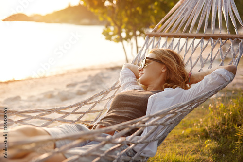 Poster de jardin Detente beautiful girl in a hammock on the beach, watching the sunset