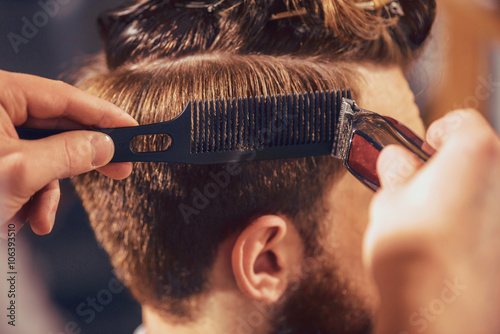 Professional barber cutting hair of his client Canvas Print