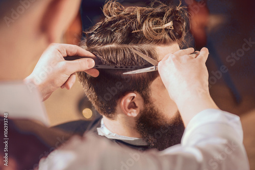 Fotografija  Professional barber styling hair of his client