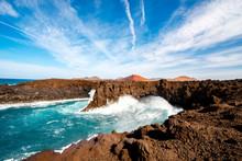Los Hervideros Rocky Coast With Wavy Ocean And Volcanos On The Background On Lanzarote Island In Spain