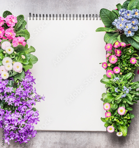Notebook with garden flowers in pots on stone background