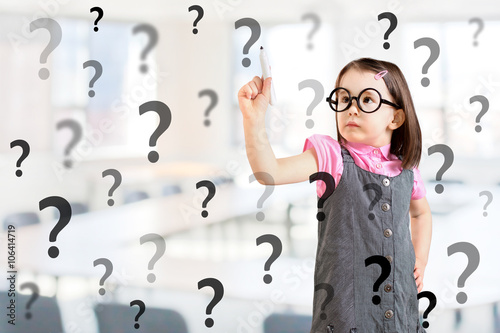 Photo Cute little girl wearing business dress and writing question mark