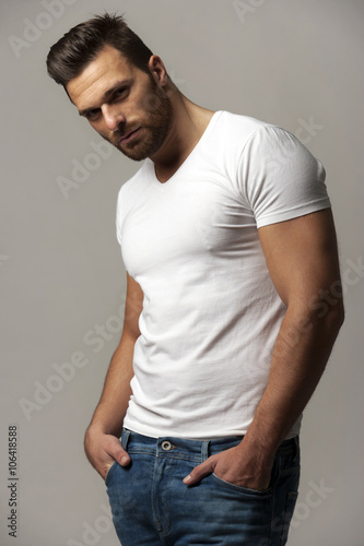 Fotografia  Handsome young man in white t shirt and jeans on gray background