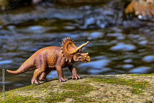 Brown Triceratops dinosaur walking with water in the background