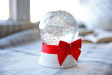 Snow Globe With Red Bow Beside...