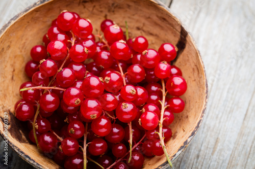 Poster Vruchten Redcurrant on a branch close to a wooden bowl.