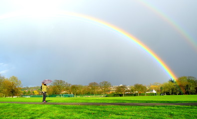 Double rainbow above park with person passing by