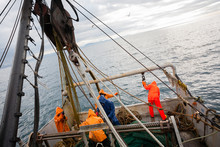Fishermen In Waterproof Clothing On The Deck Of The Fishing Vess