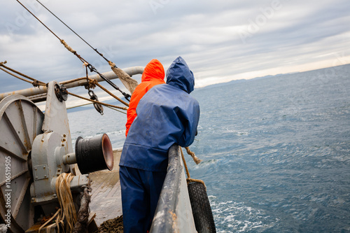Fototapeta Fishermen in waterproof suits on the deck of the fishing vessel