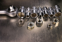 Socket Wrench And Set Of Stainless Steel Hex Sockets With Nuts On Shiny Metal Background