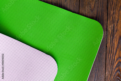 e54ab43c37ed5 New yoga mat green and white on a wooden background. Facilities for  training and yoga