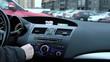 Мужчина настраивает радио автомагнитолы и регулирует громкость в автомобиле