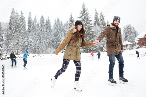 Portrait of a smiling couple ice skating outdoors Wallpaper Mural