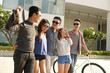 Young people in sunglasses with skateboard and bicycle standing outdoors