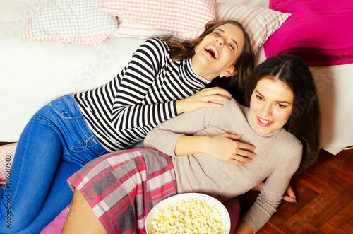 Photo  Two beautiful teenage girls eating popcorn and watching movies