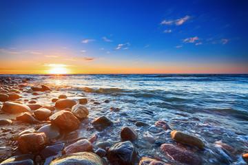 Fototapeta Optyczne powiększenie Sunset over the Baltic sea. The pebbly beach in Rozewie.