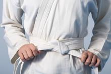 Hands Tightening White Belt On...