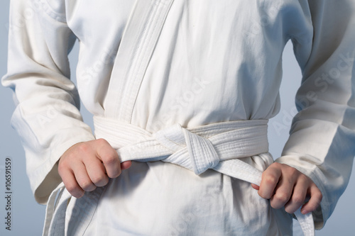 In de dag Vechtsport Hands tightening white belt on a teenage dressed in kimono for martial arts
