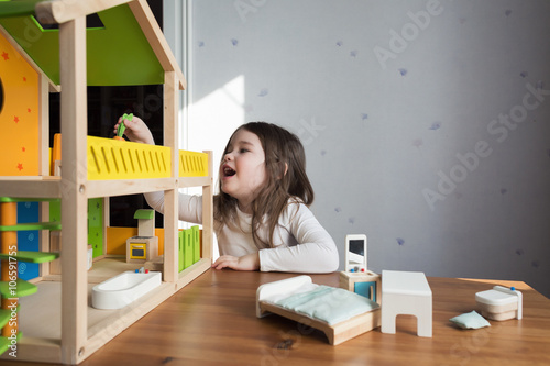 Photo  A little girl playing with her dollhouse