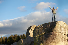 Man Standing On Rocky Outcrop ...
