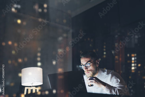 Bearded young businessman working on modern loft office at night. Man using contemporary notebook texting message, holding cup espresso, blurred background. Horizontal, film effect, bokeh