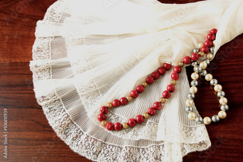 Fotografie, Tablou A white lace petticoat with a pearl necklace and a red coral necklace on a brown, wooden table