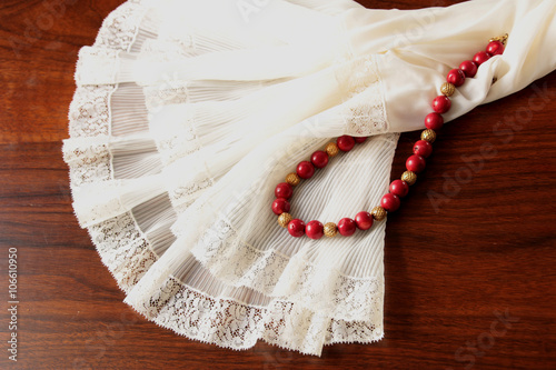 A white lace petticoat with a red coral necklace with golden spheres on a brown, wooden table Fototapet