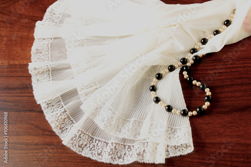 Fotografie, Obraz  A lace petticoat and a black and white pearl necklace on a brown, wooden table