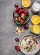 healthy breakfast cereal with dried fruits, fresh orange juice, a plate of strawberries on wooden rustic background top view