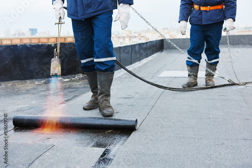 Flat roof installation. Heating and melting bitumen roofing felt Fototapeta