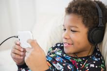Black Boy Listening To Headphones On Sofa