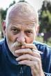 starszy mężczyzna palący papierosa