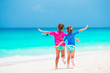 Little girls having fun at tropical beach during summer vacation playing together at shallow water