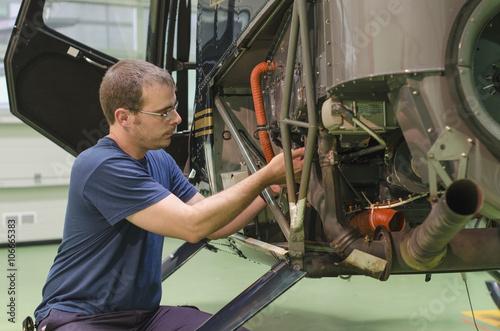 Hispanic mechanic working on helicopter in hangar