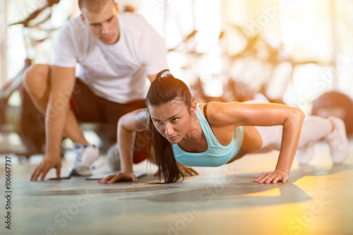 Fotografia  woman doing push ups under supervision of a trainer