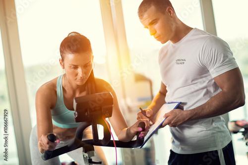 Fotografie, Obraz  Osobní trenéři v posilovně dává instrukce a pomoc, aby attr