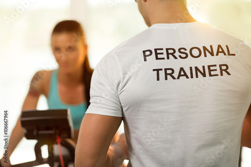 Obraz na plátne Personal trainer with woman on cycling machine at the gym