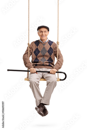 Fototapety, obrazy: Senior holding his cane and sitting on a swing