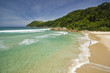beautiful tropical beach with green water and waves on shore