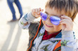 Portrait of smiling little boy putting on coloured sunglasses