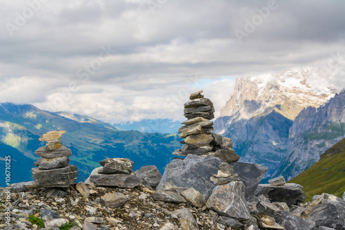 Small cairn with snow alpine mountains at background Fototapete