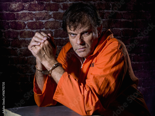 Fotografia  Mature man, handcuffed and locked in prison, with gestures of repentance