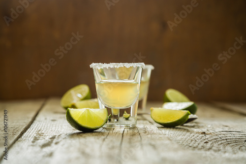 Fotografie, Obraz  Gold tequila shots on rustic wood background
