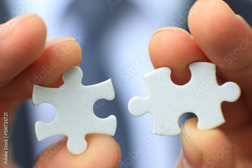 Fotografie, Obraz  Businessman holding two blank white puzzle pieces in his hands conceptual of solving a problem, growth and development
