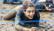 Participants in extreme obstacle race crawling under electric wire