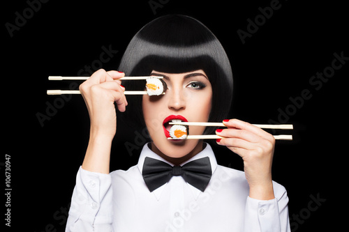 Beautiful woman eating sushi with chopsticks