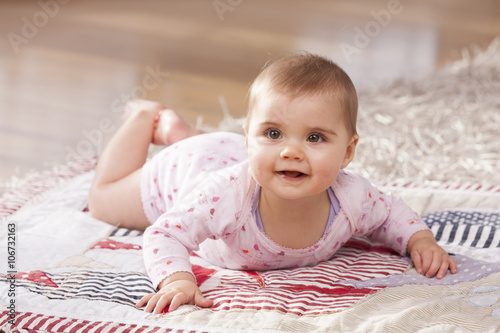 Portrait of baby girl lying on a blanket on the floor