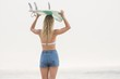 Pretty blonde woman holding a surfboard over her head